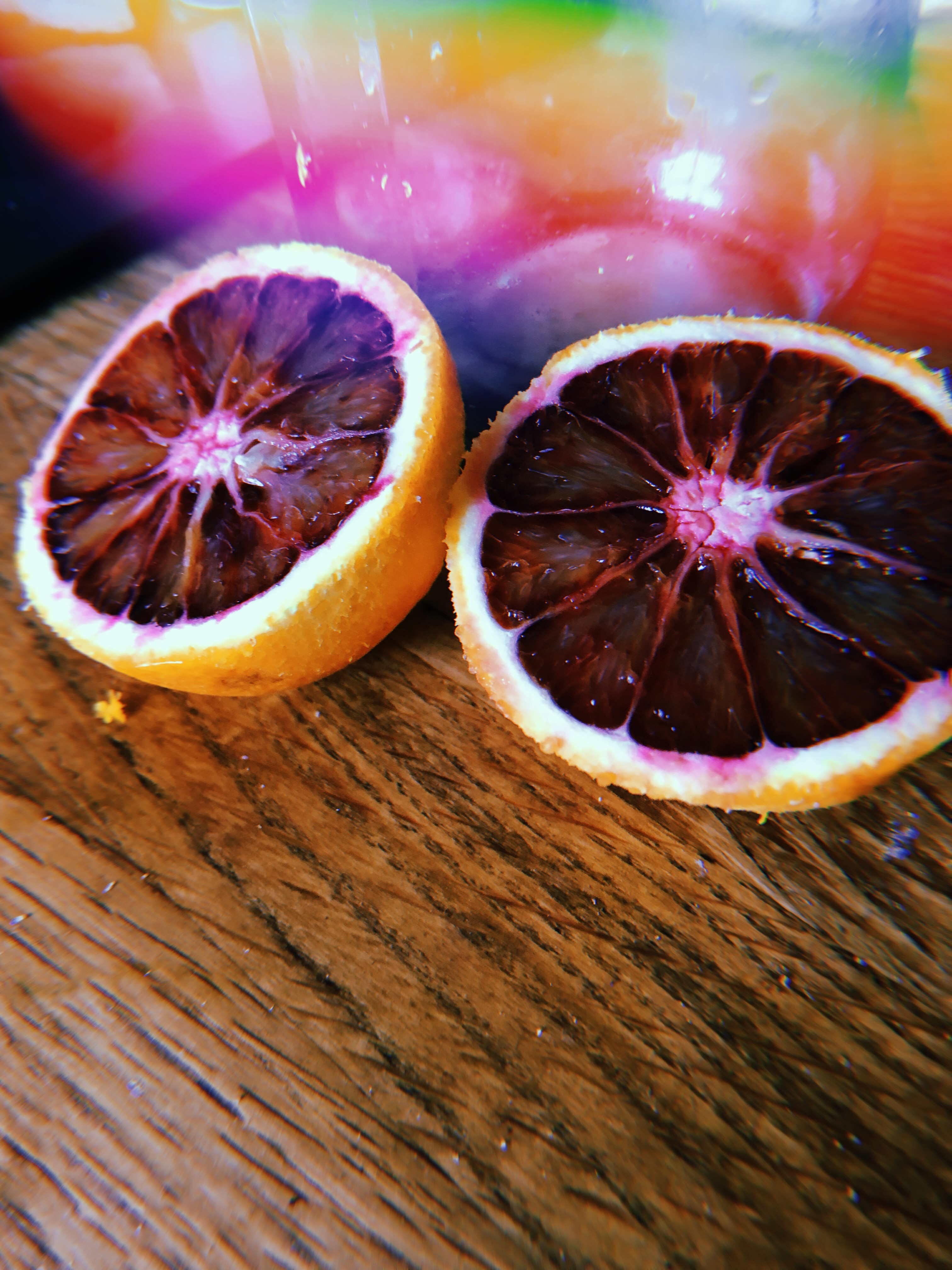 blood orange sits cut open on wooden countertop